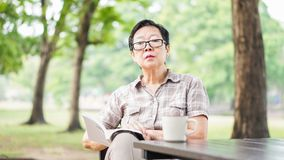 Asian senior woman reading book drinking coffee in sunny park, g Stock Photo