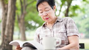Asian senior woman reading book drinking coffee in sunny park, g Royalty Free Stock Photography