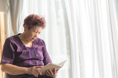 Asian senior woman reading a book with window light and vintage Royalty Free Stock Images