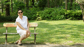 Asian senior woman sitting alone in bench park with copy space Royalty Free Stock Image