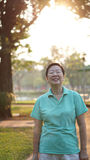 Asian senior woman smile in sunshine with morning nature backgro Royalty Free Stock Photo