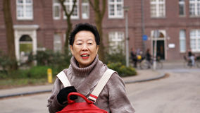 Asian senior woman smiling and having fun in her Europe travel t Royalty Free Stock Image