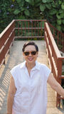 Asian senior woman smiling with sunglasses on nature walk wood deck Stock Images