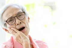Asian senior woman suffering from toothache,tooth decay,feeling pain,female elderly people holding her cheek with hand,teeth stock image