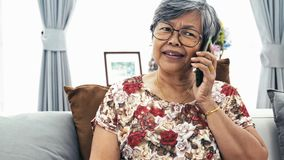Asian Senior woman talking with smart phone at home, stock footage