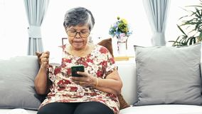 Asian Senior woman using smart phone and drinking a cup of coffee at home stock video