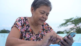 Asian senior woman using smart phone . Asian senior woman using smart phone, Happy asian old stock footage