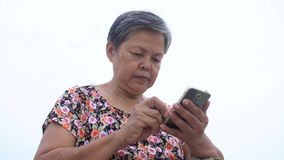 Asian senior woman using smart phone . Asian senior woman using smart phone, Happy asian old stock video footage