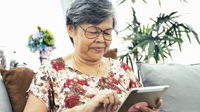 Asian Senior woman using tablet computer at home,. Happy grandmother with technology in hand .Slow motion 4K, Dolly shot stock video footage