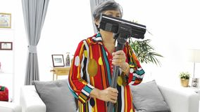 Asian senior woman vacuuming floor at home. Dancing and singing with smile face. 4K Slow motion stock video