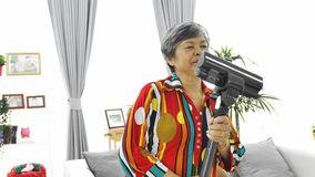 Asian senior woman vacuuming floor at home. Dancing and singing with smile face. 4K Slow motion stock video footage