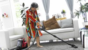 Asian senior woman vacuuming floor at home. Dancing and singing with smile face. 4K Slow motion stock footage