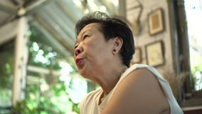 Asian senior woman worry sigh thinking at home stock video