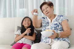 Asian senior woman eating popcorn with her grandchild. Asian senior women eating popcorn with her grandchild while watching TV at home, selective focus Royalty Free Stock Photography