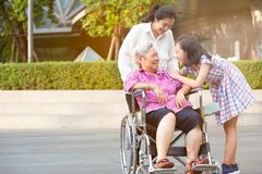 Asian senior woman having happiness and smiling with her daughter and granddaughter on wheelchair at outdoor park,elderly woman is royalty free stock photo