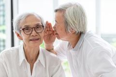 Asian senior woman holding hand near mouth telling funny,gossips on ears to friend,speaking in elderly woman ear and near face,. Asian senior women holding hand stock photo