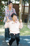 Asian senior women playing swing at outdoor garden park. 80s Asian old mother and 60s senior daughter playing swing at outdoor garden park Stock Images