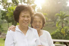 Asian seniors family having good time. Portrait of healthy Asian seniors mother and daughter sitting at outdoor nature park, morning beautiful sunlight Royalty Free Stock Photos