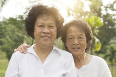 Asian seniors family at outdoor park. Portrait of healthy happy Asian seniors mother and daughter at outdoor nature park, morning beautiful sunlight background royalty free stock photo