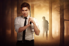 Asian serious man with a formal shirt and tie holding a gun. Asian serious men with a formal shirt and tie holding a gun ready to shoot zombies in tow royalty free stock photo