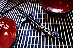 Asian set. Chopsticks and bowls on a bamboo mat Stock Images