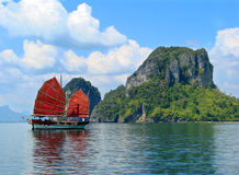 Exotic asian ship with red sails. On the background of the island and the sky. The picture was taken near the Phuket island, Thailand Royalty Free Stock Photo