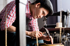 Asian shoe or belt maker in his leather workshop Royalty Free Stock Photography
