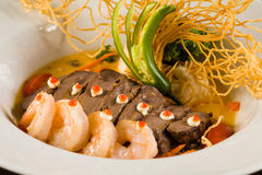 Asian Shrimp and Beef. Fancy Asian shrimp and filet mignon served with crispy noodles and vegetables on a white plate Stock Photo