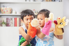 Asian sibling playing hand puppet. Asian sibling playing hand mad hand-puppet at home Stock Photography