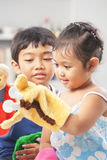 Asian sibling playing hand puppet Stock Image