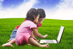 Asian sibling using laptop outdoor Stock Photos