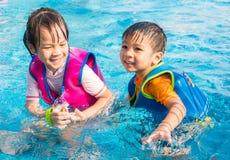 Asian siblings are having fun in pool Stock Image