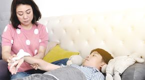 Asian Sick boy, lying in bed, mother checking his temperature.  stock photo