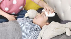 Asian Sick boy, lying in bed, mother checking his temperature.  royalty free stock photography