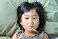 asian sick girl under blanket with temperature in mouth Royalty Free Stock Photos
