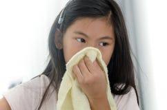 Asian sick girl using handkerchief at home. Health concept Stock Photos