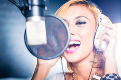 Asian singer producing song in recording studio. Asian professional musician recording new song or album CD in studio Royalty Free Stock Photography