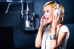 Asian singer producing song in recording studio. Asian professional musician recording new song or album CD in studio Royalty Free Stock Image