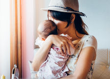 Asian single mom. Asian women hold tight and kiss her daughter's head. Vintage retro style photo with color filters, vignette effect, and some fine film noise Stock Photos