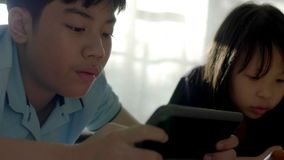 Asian sister and brother using a digital tablet together . stock footage