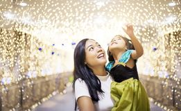Asian sister and kids joy in light decoration at night party. beautiful time to cerebrate concept. Asian sister and kids joy in light decoration at night party royalty free stock photos