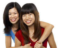 Asian sisters. Isolated on white stock images