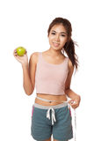 Asian slim girl with measuring tape and green apple Royalty Free Stock Photography