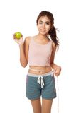 Asian slim girl with measuring tape and green apple Stock Photo