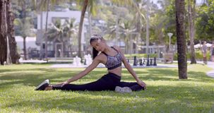 Asian slim woman stretching neck and legs sitting in park stock video footage