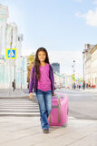 Asian small girl holding pink luggage on  street Stock Image