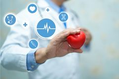 Asian smart man doctor holding a red heart : healthy strong medical concept. Asian smart man doctor holding a red heart : healthy strong medical hospital royalty free stock photo