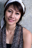 Asian smile. A beautifull woman is smiling in fornt of the wall Stock Photography