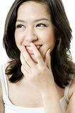 Asian Smile. An attractive young asian teenager with her hand partially covering her mouth Royalty Free Stock Photos
