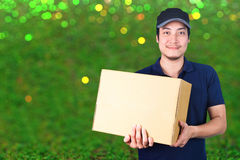 Asian smile Delivery man with cardboard box in hand standing on. Blurred green background bokeh Royalty Free Stock Image
